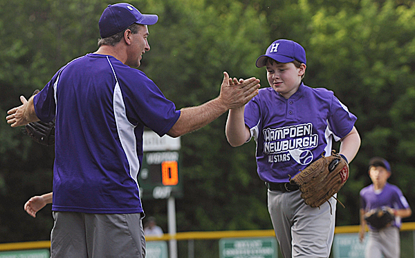 Hampden coach Brad Flannery high fives his son Zachary Flannery as well as other teammates between early innings of their Little League All-Star game for ages 10-11 at Knights of Columbus field in Old Town Tuesday, July 5, 2011.