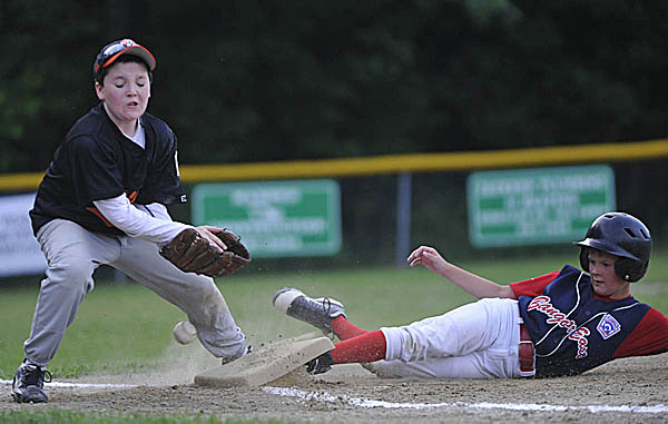 Bangor East's Zach Ireland (right) kicks up the bag before Brewer's Tyler Hersey can get the ball at third base during the fourth inning of their District 3 10-11 Little League final at Knights of Columbus Field in Old Town Monday, July 11, 2011.
