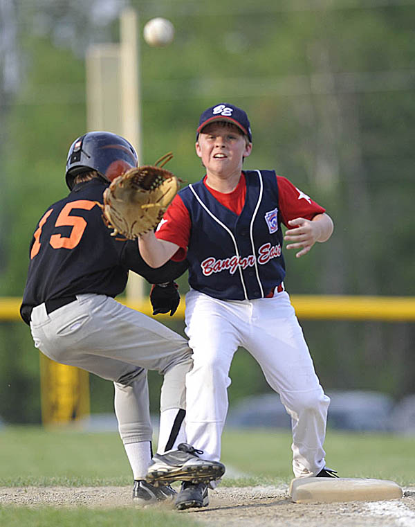 Brewer's Brandon Morinault (15) safely skirts around Bangor East first baseman Kobe Smith before he can get the ball during the third inning of their District 3 10-11 Little League final at Knights of Columbus Field in Old Town Monday, July 11, 2011.