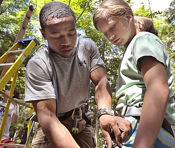 Roosevelt Boone (left), camp director of Strong Mind, Strong Body Inc., helps Bailey into her harness in preparation for the rope-climbing course at the University of Maine last week. Boone directed a weeklong wellness- and nutrition-oriented summer day camp held on the Orono campus in conjunction with the university's Conference Services Division.