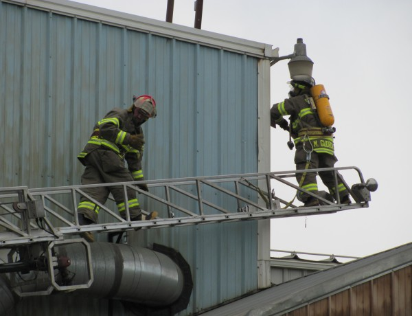 Firefighters from Dexter Fire Department tear into the side of Newport Industrial Fabrication, Inc. on Monday, July 25, 2011, to see if any flames or hot spots existed within the wall. Shown are Lt. Steve Brown Jr. (left) and firefighter Mike Gudroe. Gudroe said Dexter's ladder truck is the one of the only ones in the area and is frequently called into service for fires and emergencies involving tall buildings.