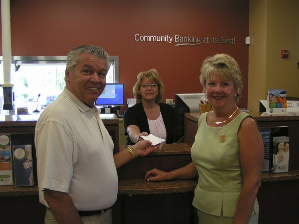 Bion (left) and Dorain Foster of Hampden, the first customers at Katahdin Trust Co.'s opening day on June 20 in Hampden, are assisted by Janet Lane, head teller at the bank's newest office on Western Avenue. The new office complements Katahdin Trust Co.'s branch in Bangor's Broadway Shopping Center and a commercial loan office at 12 Stillwater Ave., Bangor, as the bank continues with its expansion in the area. Established in 1918, the bank also operates 14 branches offices in northern Maine and a second commercial loan office in Scarborough.