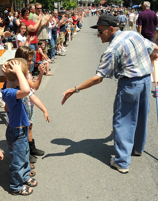 Korean War Veteran Ed Baulieu, 78, of Brewer greats children along the 4th of July Parade route in Bangor Monday.
