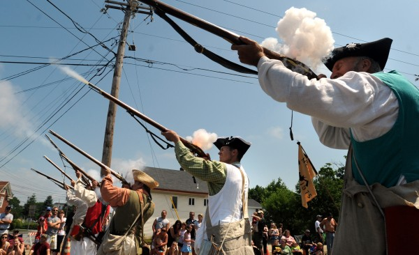 Members of the McCobbs Company of Militia reanactors shoot their rifles during the 4th of July Parade in Brewer Monday.