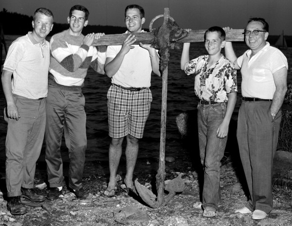 These Green Lake campers fished this large anchor from the bottom of the lake after they spotted it while swimming. It stands about 5 feet tall, weighs more than 100 pounds and is believed to be more than 100 years old. Ted Wilson (from left), Peter Purcell, Jerry Purcell and Patrick Purcell, all of Hartsdale, N.Y.; and Francis A. Finnegan of Bangor said on Aug. 7, 1960, that the anchor was found in waters off the former fish hatchery area.