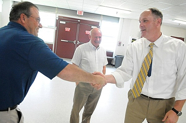Bangor High School's new principal Paul Butler (right) was congratulated by coach Mark Hackett (left) and school athletic director Steve Vanidestine while  Butler walked through the hallways at the school Thursday afternoon July 7, 2011. Butler replaces long-time principal Norris Nickerson who recently retired.