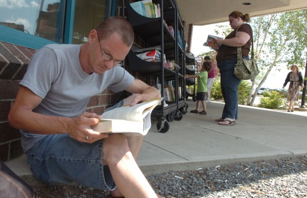Lawrence York of Bangor reads outside Borders on Tuesday. Borders announced on Monday that it would be closing its stores, which includes three locations in Maine.