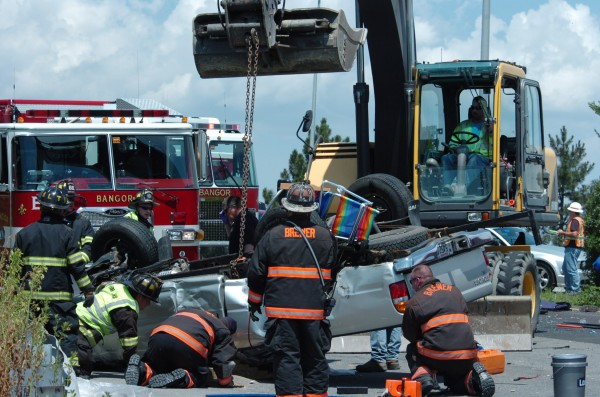 An excavator pulling on a chain steadies a rolled-over pickup truck as rescue personnel check on the victim Tuesday.