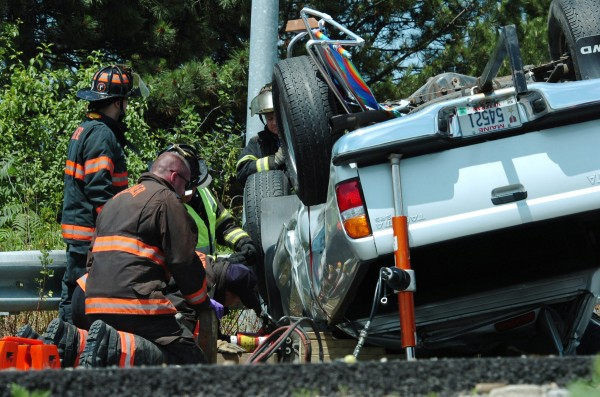 Brewer rescue personnel check on the victim in a rolled-over pickup truck in a Tuesday morning accident on the I-395 off-ramp to South Main Street in Brewer.