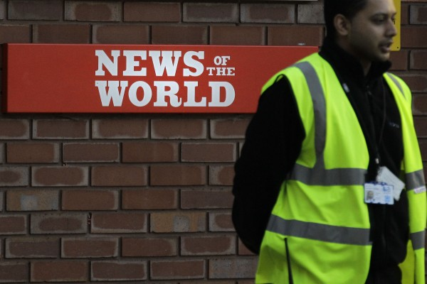 A security officer stands at the gates outside the publisher of News of the World, News International's headquarters in London, Thursday, July 7, 2011.  Sunday newspaper News of the World is accused of hacking into the mobile phones of crime victims, celebrities and politicians, prompting News International to announce Thursday that the papers is to cease publication after publication upcoming Sunday.