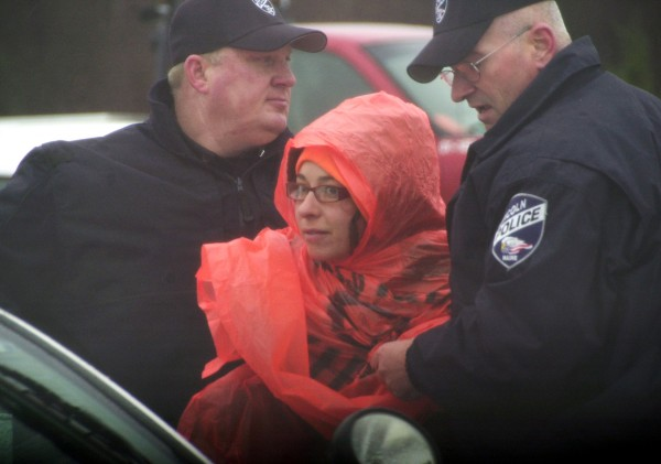 Two Lincoln police officers take Jessica Dowling, 29, into custody during a public protest of the construction of 40 1.5-megawatt wind turbines on Rollins Mountain in Lincoln in November. Protesters say they will attend Wednesday's ribbon-cutting ceremony that marks the completion of the $130 million project.