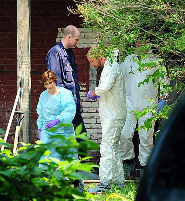 People from the Maine office of the chief medical examiner and the Maine State Police exit the first floor apartment where a body was found at 417 Main Street in Lewiston. Bob Ryder, 20, was arrested at about 3 a.m. Tuesday and held on a probation violation at Androscoggin County Jail.