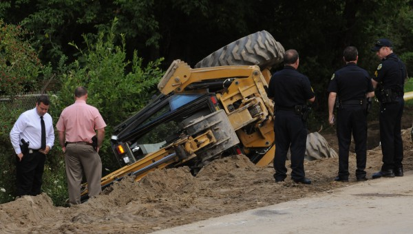 Bangor patrol officers and detectives inspect an excavator that rolled over, killing one man, on Odlin Road in Bangor on Wednesday. The construction crew was working to install a natural gas pipe line.