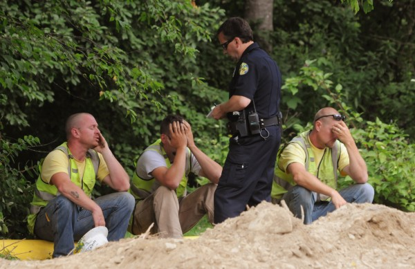 Bangor Police officer Jim Dearing, center, interviews three construction workers at the scene of a fatal excavator accident on the Odlin Road in Bangor on Wednesday.