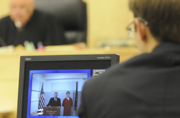 A video screen displays Danny Adams, right of Pittsfield and his attorney Aaron Frey during Adams' video appearance before Superior Court Justice Kirk Studstrup (seen in background) at Penobscot Judicial Center in Bangor Wednesday afternoon, July 13, 2011. In the foreground is legal intern Hunter Umphrey, right, who worked with Assistant District Attorney Jim Aucoin during the proceeding.