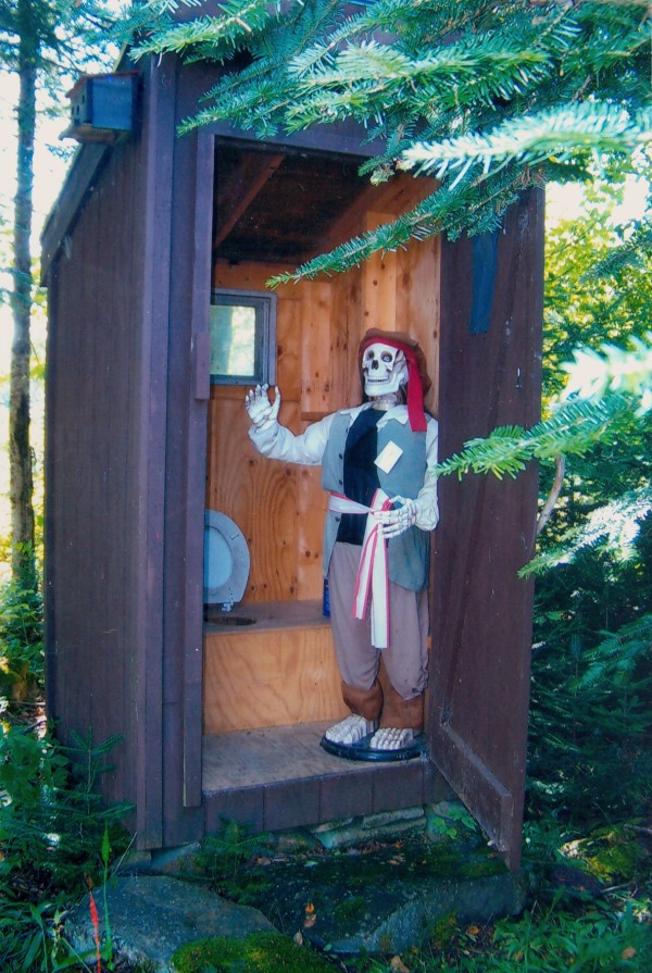 This outhouse was built 20 years ago. Two years ago at a family reunion we rigged the Halloween skeleton with a fishing line hooked to the door and hand of the skeleton to raise as you open the door.