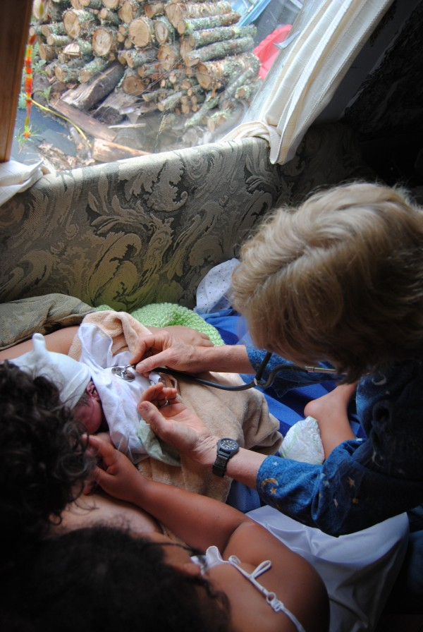 Midwife Pam Dyer Stewart of Harrington checks on Eamon James Mather moments after his birth as he is cradled by his mother, Anna Mather, of East Machias. Looking on is big sister Adiya Mather, 9.