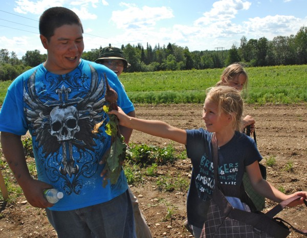 Along with healthy vegetables, the Micmac Farmers Market garden produced plenty of smiles Saturday afternoon. Visitor Emma Patterson (right) shows off a champion beet she had just picked to garden worker Moin Paul.