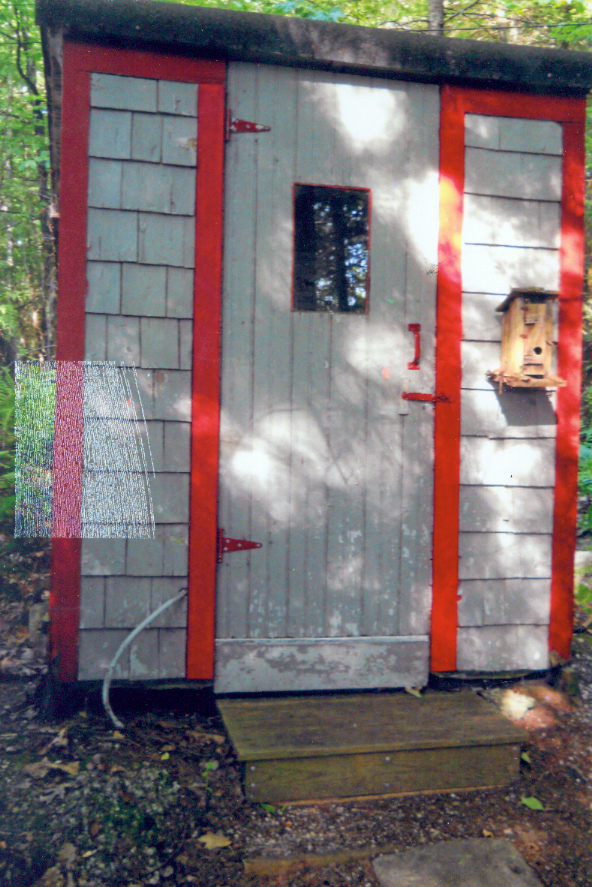 """Constructed from scrap material in 1951, this versatile outhouse has served three generations of the Smith family of Bucksport very well. Not only is it provided with a separate urinal in addition to the usual toilet seat, but both items are easily removed to facilitate easy """"dig out"""" each spring. Appropriate gender labels guide the novice to the correct facility. The windowpane built into the door allows a fine view of Lake Alamoosook while still providing the necessary privacy for the occupant. The three-shelf library is stocked with a variety of magazines and pamphlets cover a wide range of subjects."""