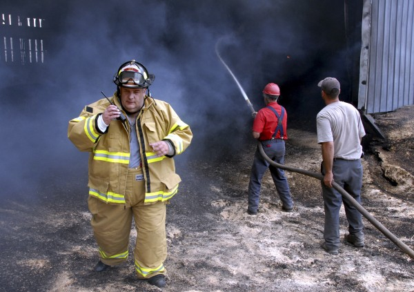 Mattawamkeag firefighter Michael Coombs listens to his two-way radio as electrician Michael Rioux and an unidentified man douse hot spots in an attached shed at the Chester Forest Products sawmill in Chester on Friday, July 15, 2011.