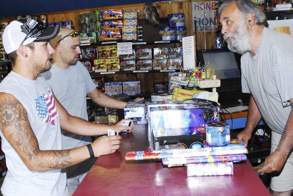 Steve Carbone, right, owner of Atomic Fireworks Inc. in Seabrook, N.H., checks out Frank Labbe, center, and Kris Kay, left, as he buys fireworks for an upcoming party. July 7, 2011.