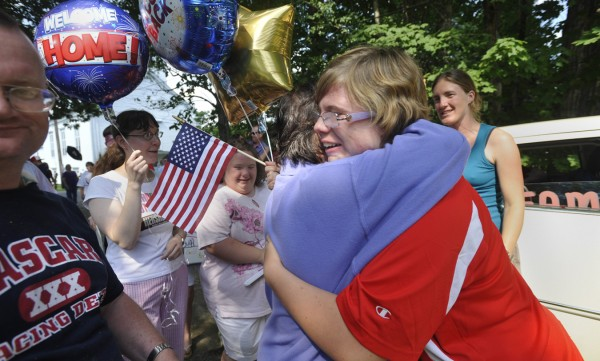 Cailynn Goss, 22, (right) got a congratulatory hug from friend Timmy Andrei of Bangor as well as other fans who gathered for her Hampden homecoming Wednesday afternoon from her Special Olympic Gold Medal swimming triumph in Greece. Goss captured the gold medal in the 50-meter butterfly during the Special Olympics World Summer Games on Sunday.