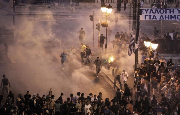 Demonstrators run away from tear gas during a demonstration in Athens on Tuesday, June 28, 2011. A general strike disrupted services across Greece and riots erupted once more outside Parliament as demonstrators protested more taxes and spending cuts essential for the country to receive critical bailout funds that will prevent a potentially disastrous default.
