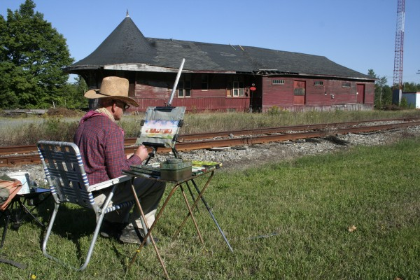 The artist Milt Christianson paints the Greenville Junction Depot. Christianson designed the logo for the depot as well.