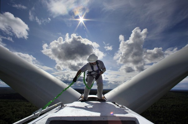 Mike Cianchette, operations manager of the Stetson Mountain wind project, checks his safety line before making inspections on top of a 300-foot tall windmill, in Township 8, Range 3, in July.