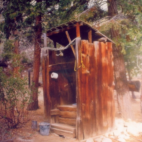 """My favorite original outhouse is one that we built IN our house … located off a hallway near the back door. It has a regular flush toilet that we encased in barn boards to look like a one-holer -- to flush, just lift the top board. It's in a tight, small space so I couldn't get far enough away to take a photo that shows the whole room at once. On the left is a shelf where I keep all my old oil lamps, which come in handy when we lost power. Hanging in the corner is the light -- an old lantern that has been electrified. As you can see in the photo, I don't dust it, so it looks more authentic. Another photo shows the outhouse rules, and the fourth photo is a picture hanging on the wall of an """"outdoor outhouse."""" Everyone who comes to visit loves our """"inhouse outhouse."""""""