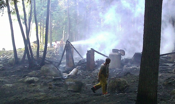 Firefighters spray water at about 6:30 p.m. Thursday, July 21, on the remains of a destroyed camp on the western side of Webb Pond.