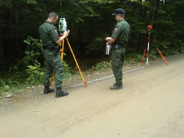 Sgt. Chris Cloutier and Warden Troy Dauphinee use Maine Warden Service survey equipment to reenact an ATV accident in Newport on Sunday afternoon. A 16-year-old male from Canaan was not wearing a helmet during the crash and remained in a drug-induced coma at Eastern Maine Medical Center in Bangor on Sunday night.
