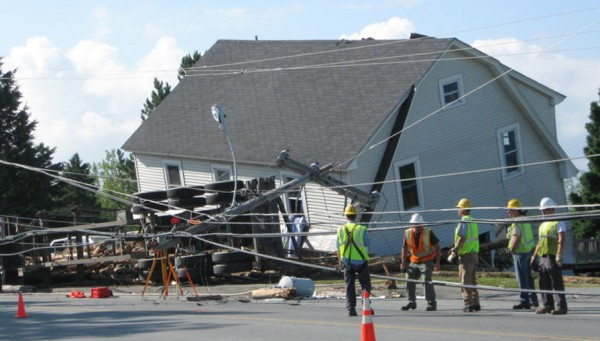 Officials survey the scene where a logging truck crashed into a home, sending logs rolling into the house and killing a 5-year-old boy in Jackman on July 19, 2011. Authorities report that the truck was passing through Jackman near the Canadian border at about 2:30 a.m. when it struck telephone poles, rolled onto its side next to the house and spilled its logs.