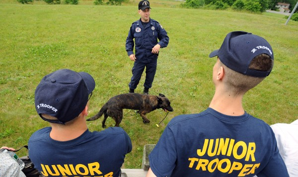 Garrett Perkins (left), 18, of Wells and Anthony Connolly, 18, of Portland listen to Trooper Scott Dalton talking about Spike, the five-year-old Dutch shepherd that serves with the State Police K-9 unit.