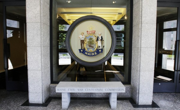 In this July 13, 2011 photo, the reflection of a capitol security officer (left) is seen at an entrance to the State House in Augusta. Visitors to the Maine State House, and many of those who spend a lot of time there, may be in for something of a surprise. Long known for its open doors and low level of security, the State House will soon have two walk-through metal detectors and X-ray machines at its main entrance. The Capitol Police Chief says the move to tighter security is part of a national trend.