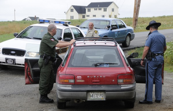 Warden Josh Tibbetts (from left), Penobscot Sheriffs Deputy James Kennedy and Maine State Trooper Douglas Franklin compared notes as they looked over a red Suburu driven by Paul Flynn (not pictured), 50, of Albion whom they stopped and arrested on the corner of Pine Tree Road and Fuller Road. in Levant on Tuesday morning, July 26, 2011. Flynn, who was wanted by area police, tried to buy liquor at the Levant Corner Store just minutes earlier.