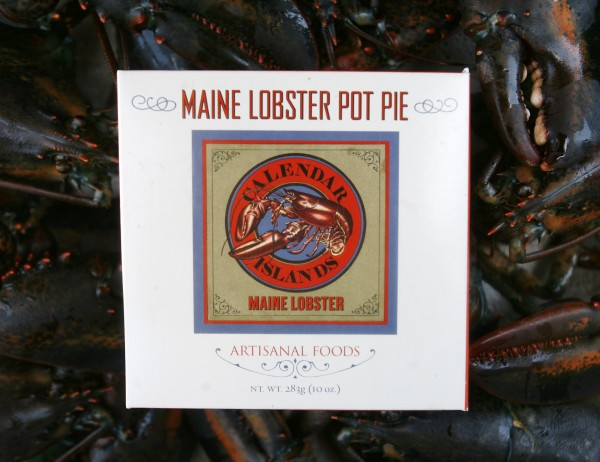 A frozen lobster pot pie package is posed by a bunch of live lobsters near the wharf in Portland recently.