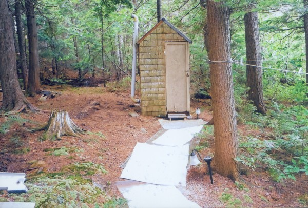 "Ervin Marston of Bangor said this is a picture of ""our outhouse on Millinocket. After 50 years of havinga two-holer we have converted to a one-holer which is almost like our one at home except no flushing. It is also a convenient height off the floor for the over 70 folks. As you can see the Reader's Digest is our book of choice with short stories. The unique thing about our outhouse is we have a big window that we can enjoy a beautiful view of Mt. Katahdin while doing our business."