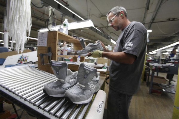 Kirby Knox inspects a 993 shoe at the New Balance shoe factory in Norridgewock. The company could make far more money if, like Nike and Adidas, it shifted most of these jobs to low-wage countries.