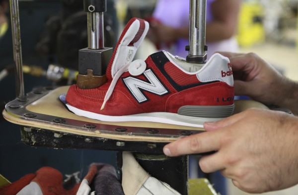 A worker uses a press to attach a shoe upper to the outsole at the New Balance factory in Norridgewock. The Obama administration is negotiating a free-trade agreement with Vietnam and seven other countries, and it is unclear whether the New Balance plant can stand up to a flood of shoes from that country, already one of the leading exporters of footwear to the United States.