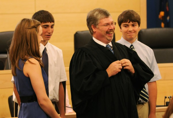 New district court judge Greg Campbell grins as he faces a packed courtroom after donning judge's robes for the first time on Friday in Bangor.