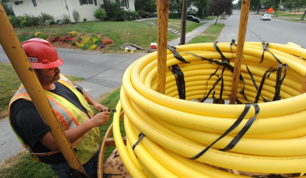 """Andy Mooney, a foreman with the Ypsilanti, Michigan-based InfraSource, cuts tape from a 2-inch gas line they were laying on Norway Road in Bangor.  """"Depending on the conditions, we can lay 500-1,000 feet of line in a day,"""" said Mooney. The lines are being installed for Bangor Natural Gas Company."""