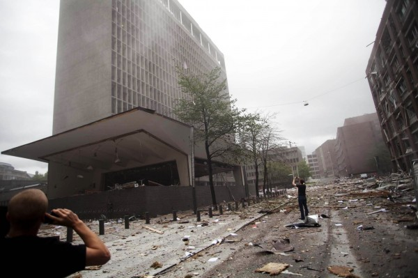 Debris covers the street outside buildings in the centre of Oslo, Friday July 22, 2011, following an explosion that tore open several buildings including the prime minister's office, shattering windows and covering the street with documents.