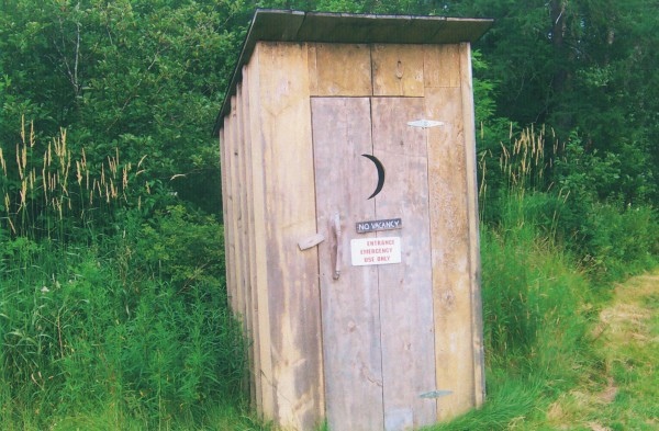 "This outhouse, said Berwyn Peasley of Brooksville, was made from scrap lumber, boarded and batted like the old times. ""The toilet seat was a three-holer, used int he Penobscot Town Hall (1901) many years ago. We cut it to make a two-holer because the other had rotted away. Real pleasure to set on. It was built for comfort not speed.The door hendle was made from a spruce limb.the curtain made from burlap for security. The outhouse is located at the Penobscot Historical Society, between the schoolhouse and the main house."""