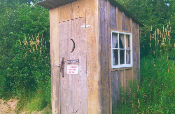 """This outhouse, said Berwyn Peasley of Brooksville, was made from scrap lumber, boarded and batted like the old times. """"The toilet seat was a three-holer, used int he Penobscot Town Hall (1901) many years ago. We cut it to make a two-holer because the other had rotted away. Real pleasure to set on. It was built for comfort not speed.The door hendle was made from a spruce limb.the curtain made from burlap for security. The outhouse is located at the Penobscot Historical Society, between the schoolhouse and the main house."""""""