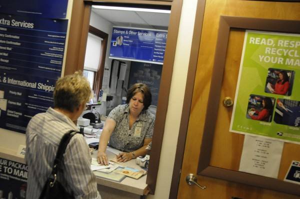 East Newport acting postmaster Barbara Henkle assists Regina Graves, left, of Etna with her postage in July.