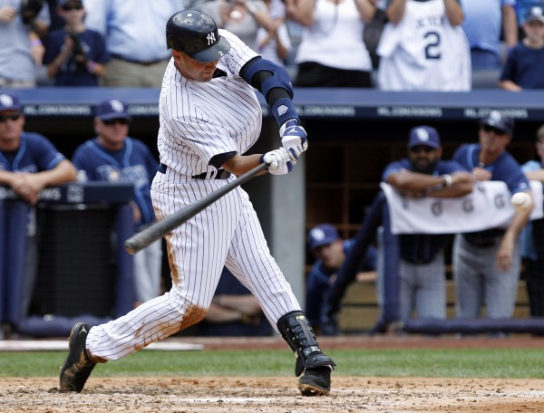 New York Yankees' Derek Jeter follows through on a home run for his 3,000th hit during the third inning of a baseball game against the Tampa Bay Rays, Saturday, July 9, 2011, at Yankee Stadium in New York. Jeter is the first Yankees player to reach the milestone.