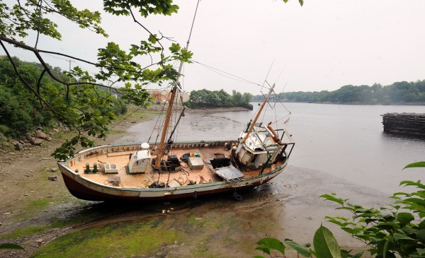 The Roamer lays in the mud along the west bank of the Penobscot River in Hampden.