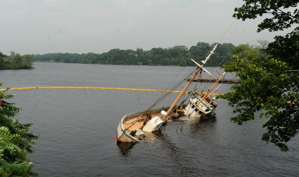 The Roamer rests on its side aground along the west bank of the Penobscot River in Hampden. As the tide came in, the boat did not refloat and appeared to have filled with water. The Maine Department of Enviromental Protection placed a floating containment boom around the vessel.