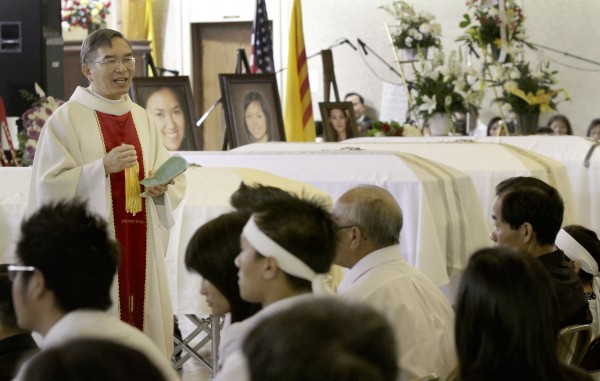 Rev. Peter Quang Le, left, of the Sacred Heart of Mary Church in Barling, Ark., on Saturday, July 30, 2011, conducts a service for four of the five victims of a shooting rampage last weekend at a Grand Prairie, Texas roller rink. Trini Do, 29, her sisters, Lynn Ta, 16, and Michelle Ta, 28, and her brother, Hien Ta, 21, were killed when her estranged husband opened fire during a birthday party for the couple's 11-year-old son. Tan Do, 35, later killed himself. Trini Do received a protective order in December against her husband, but she had it withdrawn earlier this year against a prosecutor's advice because she wanted to give him another chance, an aunt has said.